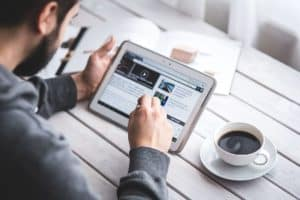 man-reading-touchscreen-blog
