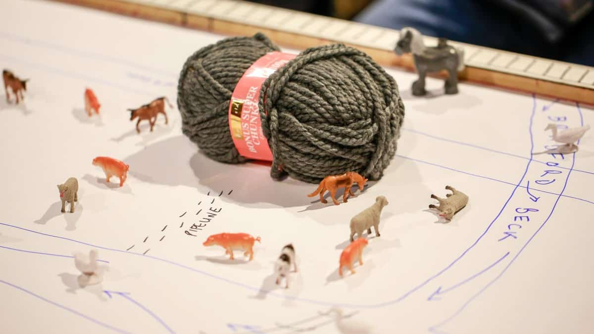 Toy sheep around a ball of wool